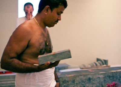 Shiva Kumar, supervising Sthapati, holds the next stone to be placed.